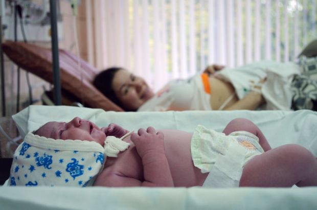 36791602 - newborn baby at desk next to her mother in the maternity hospital